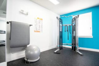Gym's corner equipment next to a windows and reflecting mirror