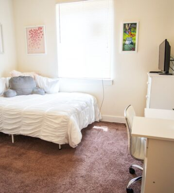 Student bedroom side view with furniture , picture frames and gray pillow in bed